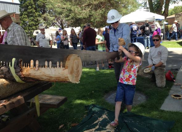 Jen helps a shorty work the crosscut saw. What a gal!