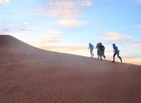 Members of SCA's Canyon de Chelly Crew run up a sand dune in the fading hours of daylight