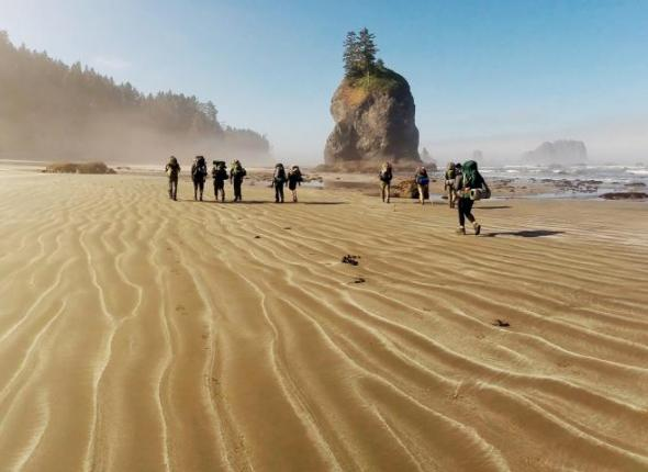 An SCA crew walks along an empty beach in Olympic National Park's coastal wilderness. They worked with NOAA to clean up marine debris in the area.