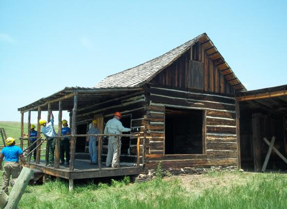 SCA and BKNF staff apply linseed oil to Miller Cabin exterior